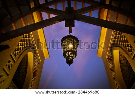 Arabic lantern hanging from a giant wooden arch. below angle. - stock photo