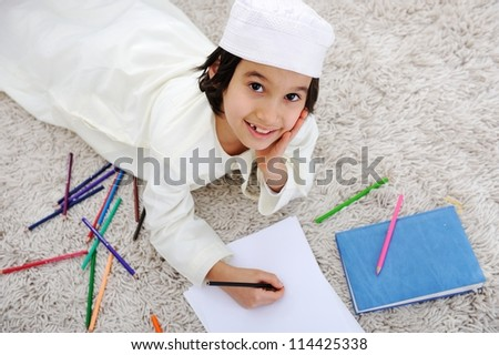 Arabic little boy doing homework at home - stock photo