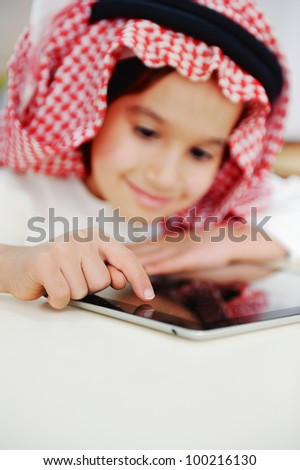 Arabic little boy playing on tablet - stock photo