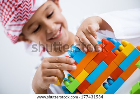 Arabic little boy playing with toys - stock photo