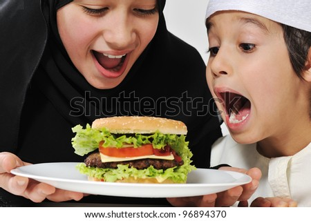 Arabic little male and female eating Burger - stock photo