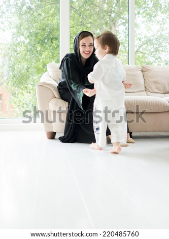 Arabic mother with baby at home - stock photo