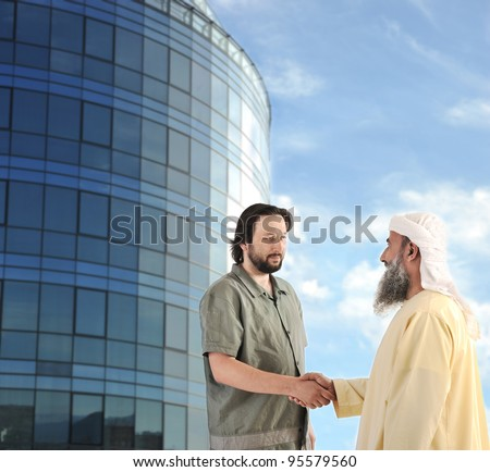 Arabic Muslim businessman meeting outdoors in front of modern building - stock photo