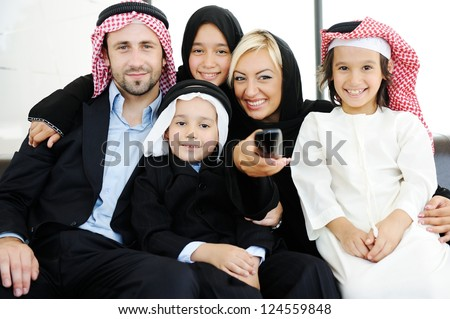 Arabic Muslim family father and mother with children watching television - stock photo