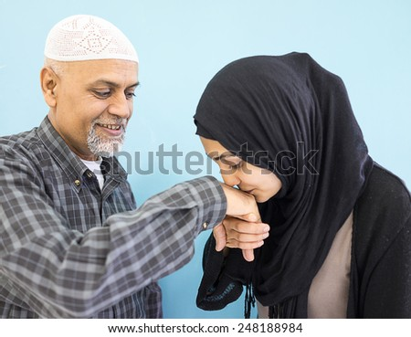 Arabic Muslim girl with her father kissing his hand for respect - stock photo