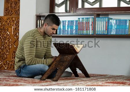 Arabic Muslim Man Reading Holy Islamic Book Koran - stock photo