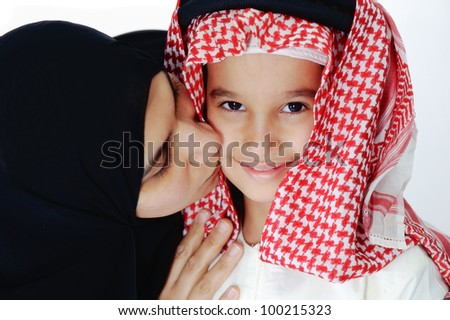 Arabic Muslim mother kissing her little son