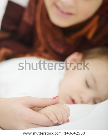 Arabic Muslim mother playing and taking care of her baby - stock photo
