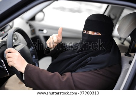 Arabic Muslim woman driving a car and happy for that - stock photo