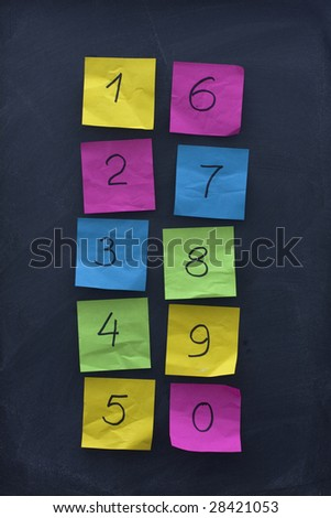 arabic numerals from zero to nine handwritten on colorful crumbled sticky notes and posted on blackboard with eraser smudges - stock photo
