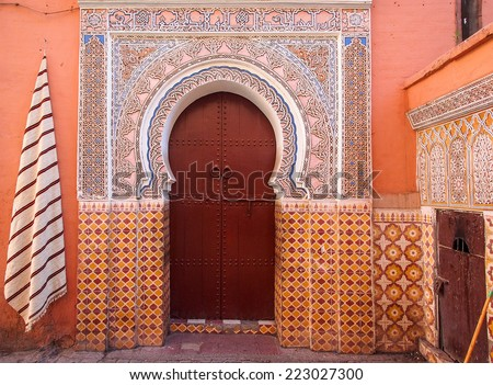 Arabic old style door to a house in an orange wall - stock photo