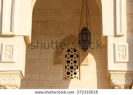 Arabic Patterned narrow window on an old stone wall with an ancient lamp hanging near, Egypt - stock photo