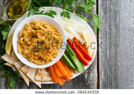 Arabic sauce hummus with flatbread and fresh vegetables on wooden background, top view