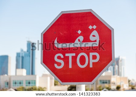 Arabic Stop Sign, United Arab Emirates, against cityscape.