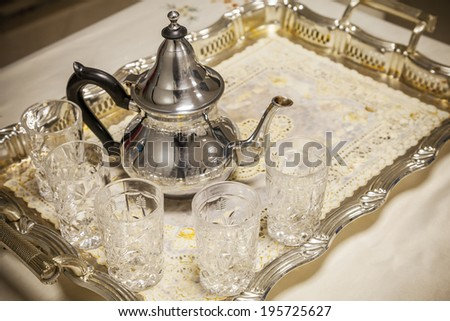 Arabic tea theme. Teapot with glasses on metal salver