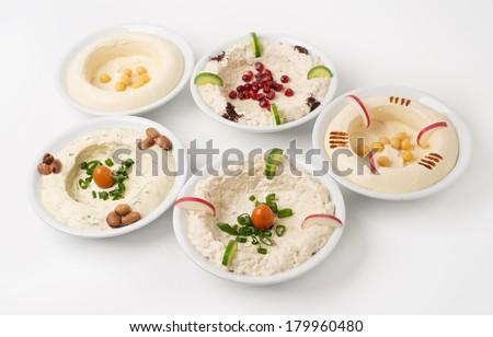 Arabic traditional Hummus Plates with different toppings isolated on white  - stock photo