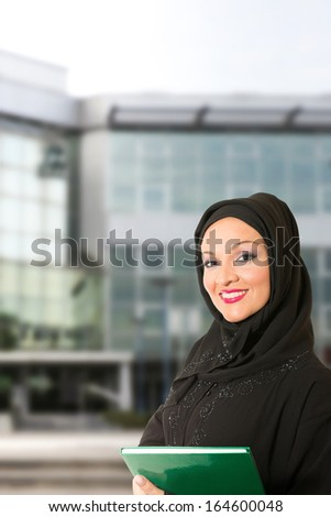 Arabic woman, traditional dressed, standing in front of the building. - stock photo