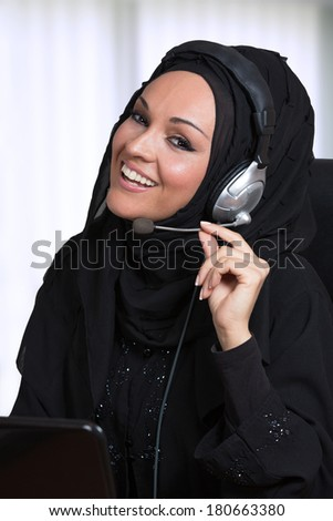 Arabic woman, traditional dressed, working as a customer service, inside her office. - stock photo