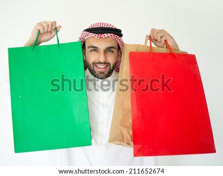 Arabic young businessman with shopping bags - stock photo