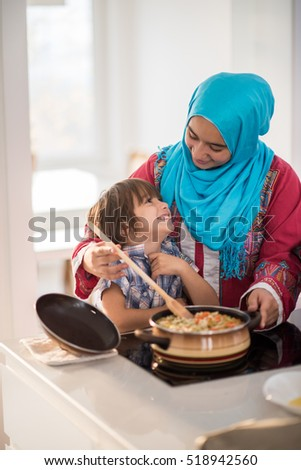 Arabic young woman with little kid in kitchen