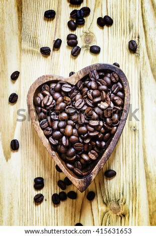 Arabica Coffee beans in a wooden bowl in the shape of a heart, a top view