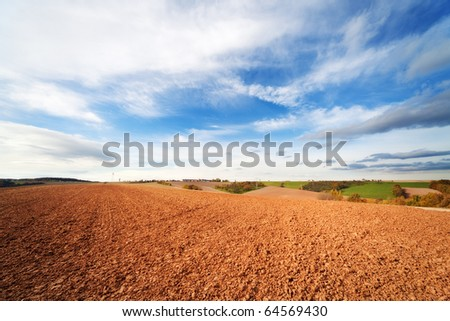 arable land in spring time and blue sky - stock photo