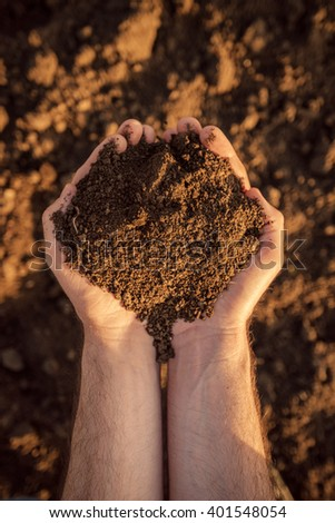 Arable land soil in hands of a responsible farmer, male caucasian farmer holding pile of soil, agronomist preparing land for new crop raising season, close up of hands. - stock photo