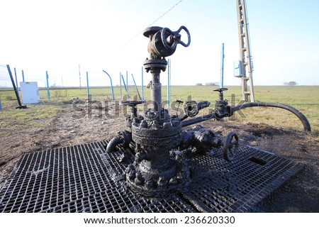 ARAD, ROMANIA - FRIDAY, DECEMBER 5, 2014: Oil leaks from a surface well head at a production field operated by OMV Petrom S.A, the largest gas and oil producer in Eastern Europe - stock photo