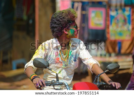 ARAMBOL, GOA, INDIA - MARCH 17: Unidentified man celebrates Holi festival in Arambol Main Street, GOA, India on March 17, 2014. It's a religious spring holiday and also known as Festival of Colours.  - stock photo