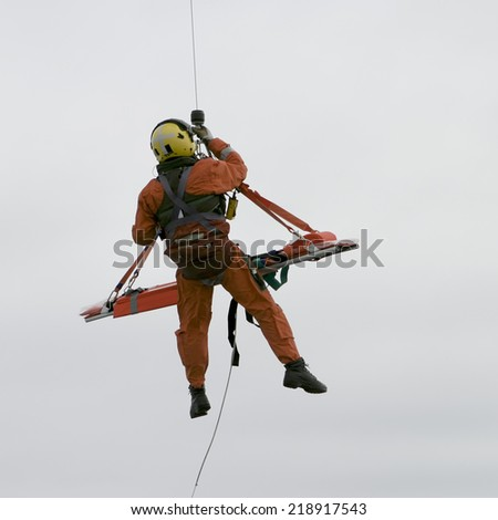 ARAN ISLANDS, IRELAND - JULY 2, 2006: An Irish coast guard search and rescue mission shows a dangling guardsman in an orange uniform bringing the stretcher up to the helicopter near the Aran Islands.