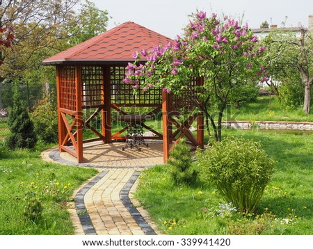 Arbor in garden with lilac horizontal - stock photo