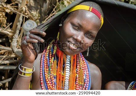 ARBORE, ETHIOPIA, 13AUGUST:unidentified young woman from Arbore tribe in Arbore, Ethiopia, on 13 august 2014. Arbore women use black veils as clothes and a lot of bead necklaces as personal decoration - stock photo