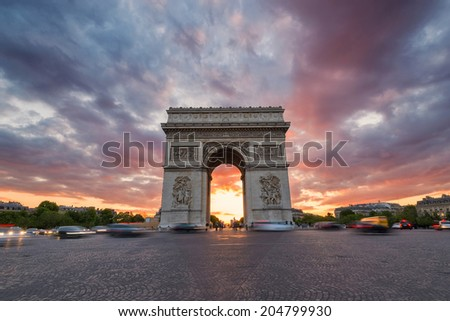 Arc de Triomphe and traffic along the Champs-Elysees at sunset with dramatic sky. The Champs Elysees is the most famous street in Paris.