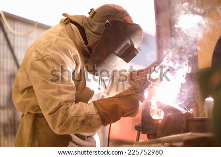 Arc welder on work with protective helmet - stock photo