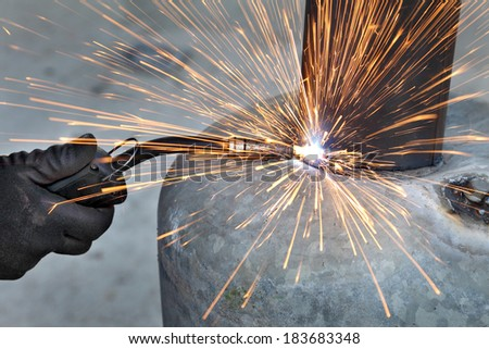 Arc welding of a steel, welder hands in gloves, tool and sparks - stock photo