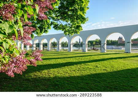 Arcade of the ancient Yaroslav's courtyard framed by blooming lilac in Veliky Novgorod (Russia)