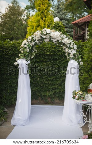Arch and two white chairs in golf club prepared for weeding. Donetsk, Ukraine