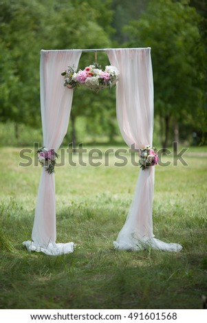 arch for wedding ceremony the bright fabrics on a background of green grass in summer Park