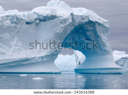 Arch Shaped Iceberg in Antarctica - stock photo