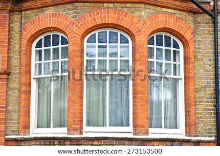 Arch windows in a red brick building in London, UK - stock photo