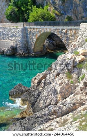 Arched bridge across sunny green waters of the Adriatic sea, Trsteno,  Croatia - stock photo