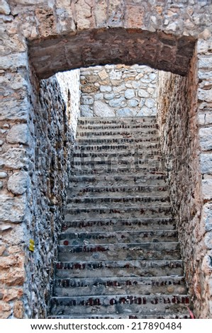 Arched entrance to an ascending flight of old stone steps bordered by exterior natural rough stone or rock walls in an architectural background - stock photo