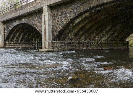 Arched Stone Bridge across wide stream