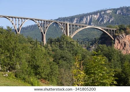 Arched Tara Bridge over green Tara Canyon. Zabljak, Montenegro. - stock photo