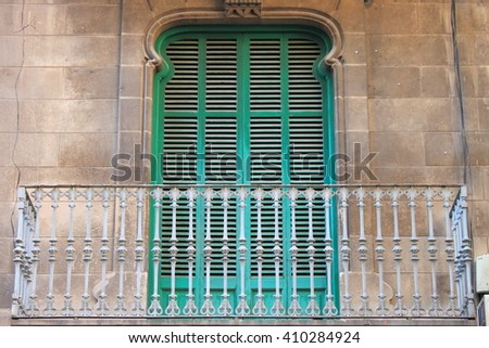 Arched window with closed shutters and balcony - stock photo