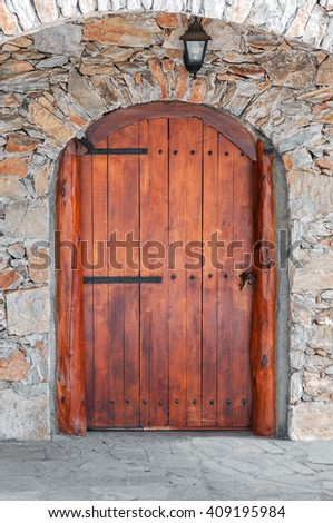 Arched wooden door in a stone wall - stock photo