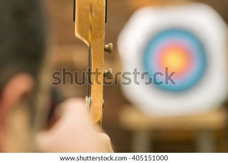 Archer aiming against the blurred target. - stock photo