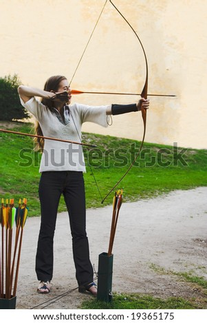 archer beauty girl plays arrow bow shooting sport stay side view position concentration - stock photo
