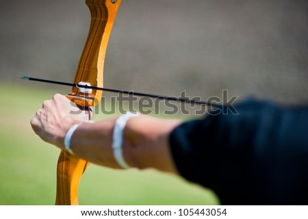 Archer holds his bow aiming at a target - stock photo