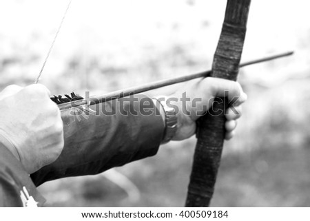 Archer holds his bow, black and white photo - stock photo